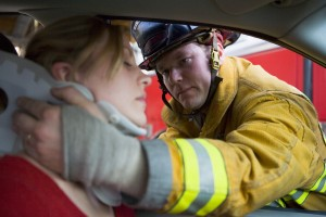 firefighter helping woman in car accident
