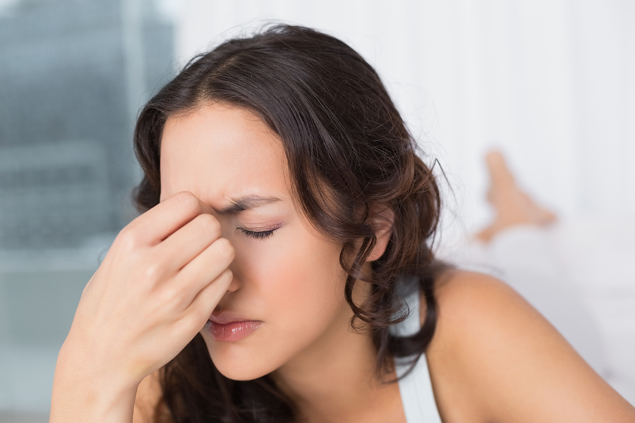 Headache Woman - Early Warning Signs of a Bed Bug Infestation